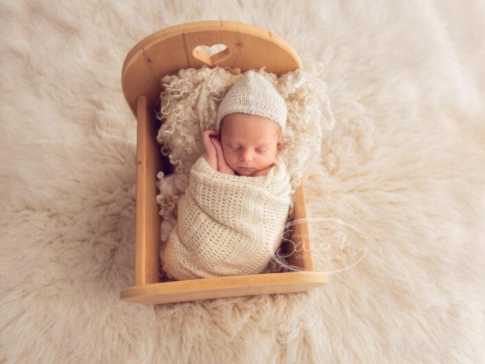pasgeboren baby in bedje, newbornshoot