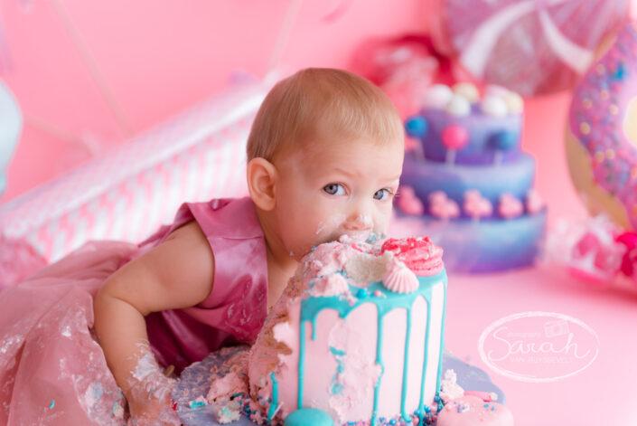 Baby bijt in taart, baby viert eerste verjaardag met taart, baby eet taart,smashcake